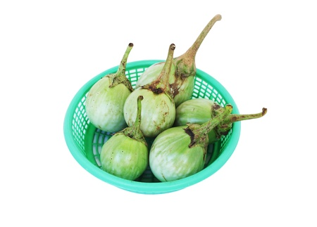 Green eggplants in the basket isolated on white background
