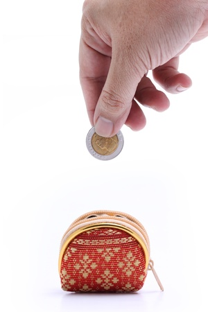 gesture of hand drop coin into the Thailand pattern coin bag