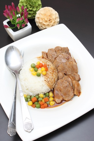 Thai food, Slices of roasted pork and sauce and vegetable with rice in white plate photo