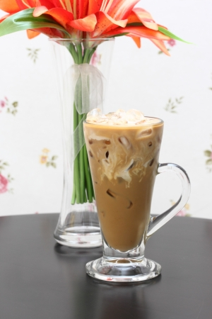 Glass of ice coffee and milk with fabric flower in glass vase