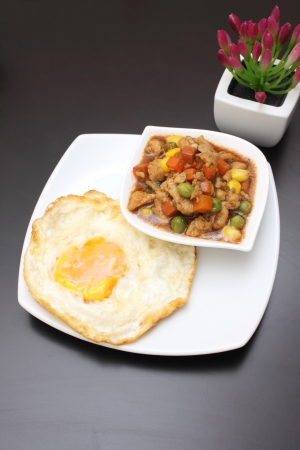Thai food, minced pork sauce and vegetable with fried egg in white plate on wood black table Stock Photo