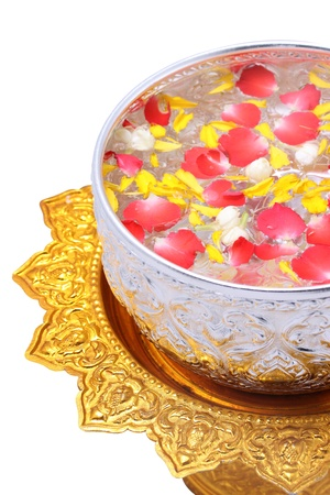 Water in water dipper with colorful flowers corolla on golden tray with pedestal for Songkran festival, Thailand Standard-Bild