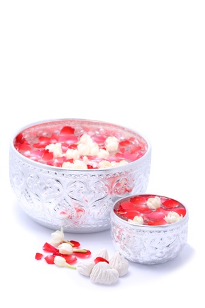 Water with jusmine and roses corolla in big and small bowl and soft-prepared chalk for Songkran festival, Thailand Stock Photo
