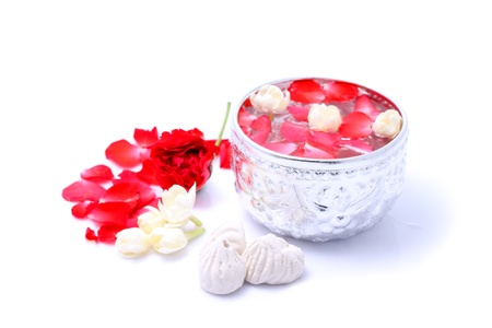 Water with jusmine and roses corolla in bowl and soft-prepared chalk for Songkran festival, Thailand
