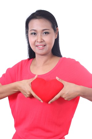 dishy: Young woman holding a heart shaped red pillow, isolated on white background.