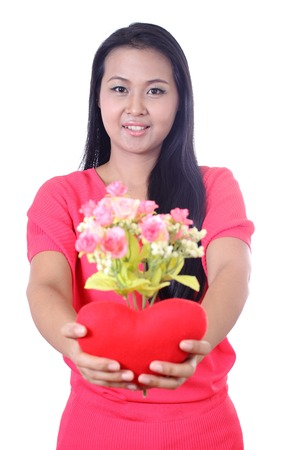 Young woman holding artificial flower and  heart shaped red pillow, isolated on white background. photo