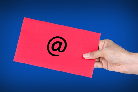Hand holding red envelope with at Symbol, concept of E-Mail