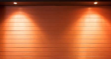 Illuminating pot-lights shining down on a wooden wall photo