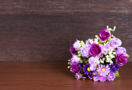 Colorful artificial flower on wood background photo