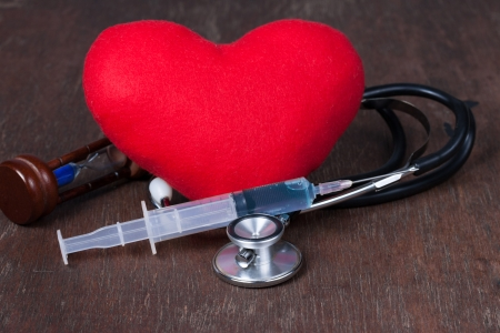 Medical, Group of objects on wood table. red heart ,stethoscope,syringe ,hourglass photo