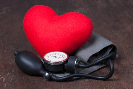 Medical, measure blood pressure with red heart on wood table Stock Photo