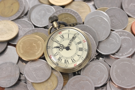 Financial concept, old watch with coins photo