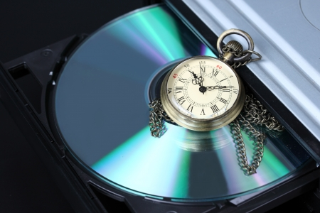 Time concept, old watch with open DVD tray