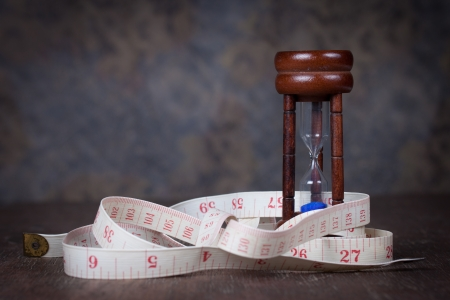 Hourglass with tape measure on wood table photo
