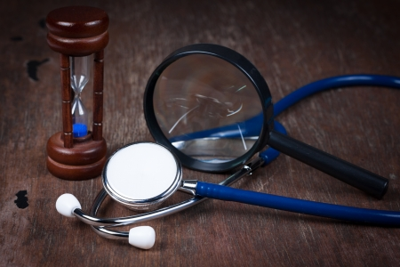 Medical concept , Group of objects on wood table. hourglass , stethoscope, magnifying glass photo