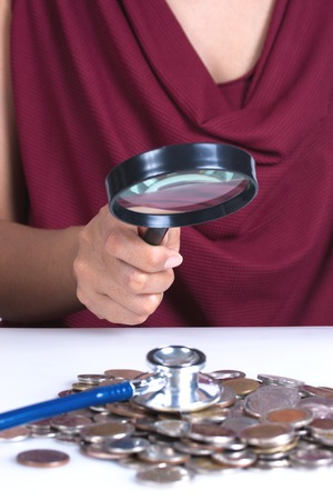 Financial concept, hand hold magnifying glass and coins Stock Photo