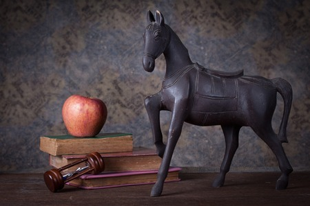 Group of objects on wood table  old wood horse, hourglass, old books , red apple, Still life photo