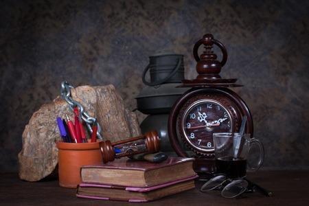 Group of objects on wood table  old clock, old books, rock ,glasses, pencil, pen, old rusty kerosene lamp, glass of coffee, Still life photo