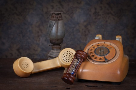 Group of objects on wood table.  hourglass, old  telephone, old rusty kerosene lamp photo