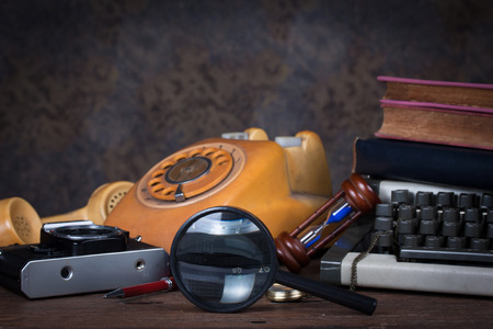Group of objects on wood table. magnifying glass, old telephone, type writer, old camera, Still life photo