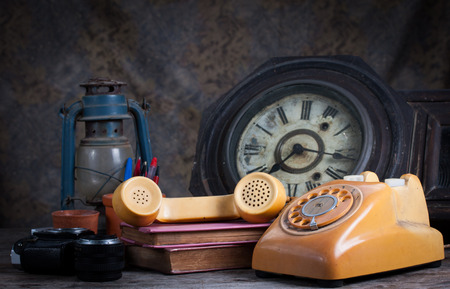 Group of objects on wood table. old telephone, type writer, old camera, Still life photo