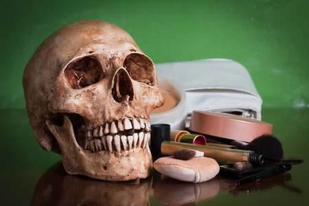 Weathered human skull with makeup brush and cosmetics. photo