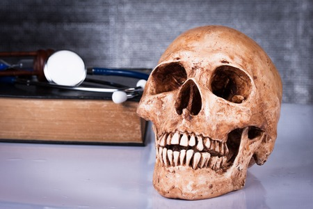 Medical concept, weathered human skull and stethoscope photo