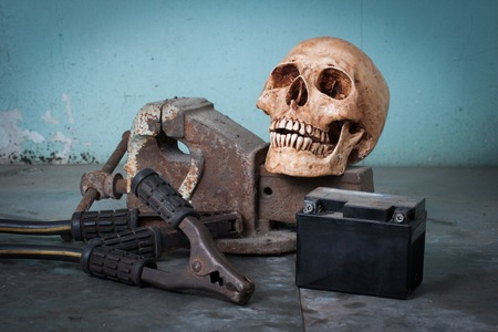 Group of objects on table. human skull, bench vise, jumper cables, car battery photo