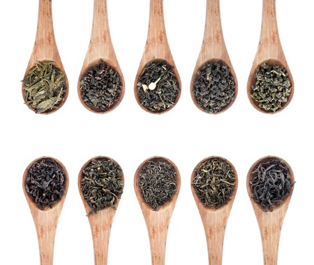 assortment of dry tea in wooden spoon, isolated on white background