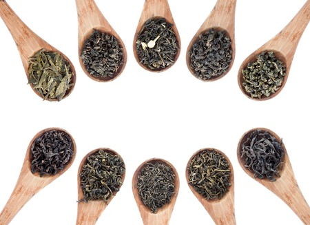 assortment of dry tea in wooden spoon, isolated on white background photo