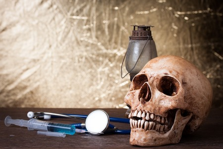 Medical concept , Weathered human skull and syringe
