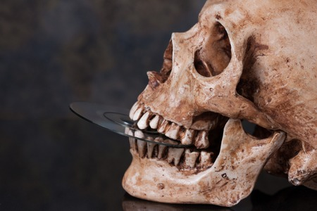 Human skull and dvd in mouth