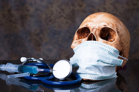 Group of objects on a granite, Stethoscope , syringe, human skull with mask ,Medical concept photo