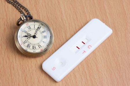 test deadline: Pocket watch with pregnancy test on wooden table, Time to born , concept idea