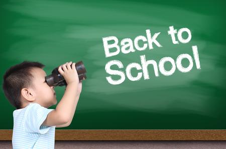 using binoculars: Boy using binoculars with green chalk board