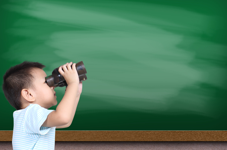 using binoculars: Boy using binoculars with green chalk board