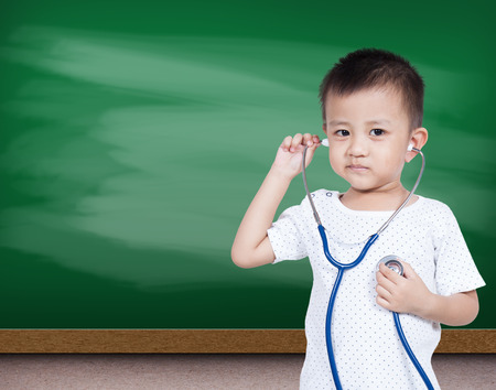 Little asia boy holding stethoscope with green chalk board