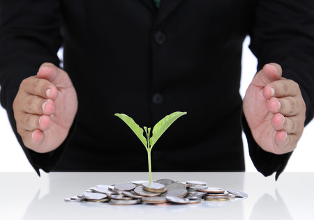 Businessman hand protect money for safe investment in the future. Stock Photo