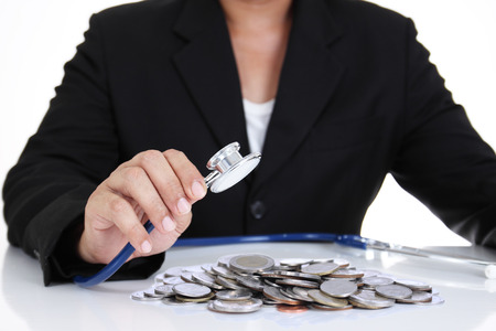 Businessman holding stethoscope with coins Stock Photo