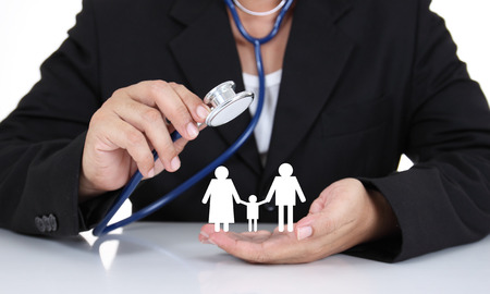 Businessman holding stethoscope with paper family