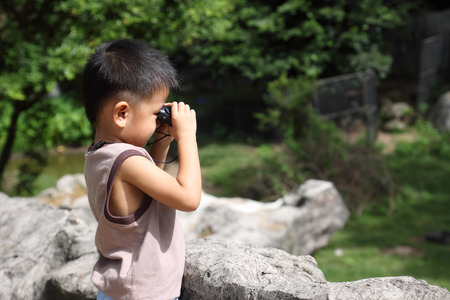 using binoculars: Boy using binoculars looking for something