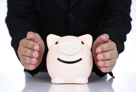 safe investments: Mano dell'uomo d'affari protegge denaro per gli investimenti al sicuro per il futuro.