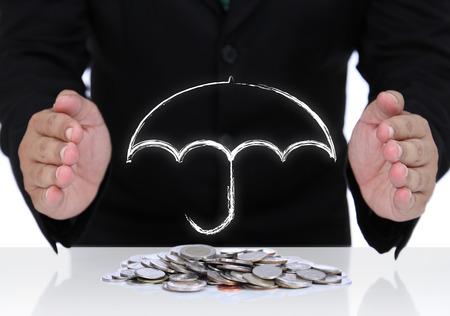 safe investments: Businessman mano proteggere soldi con ombrello bianco segno per investimento sicuro per il futuro.