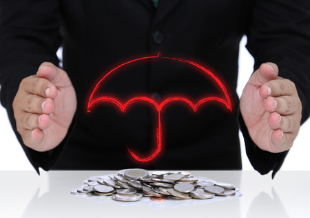 Businessman hand protect money with red umbrella sign for safe investment in the future. photo