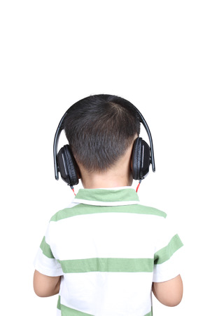 Back view kid listening to music on headphones, isolated on white background