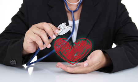 Businessman holding stethoscope with heart sign photo