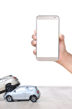 woman hands use cell phone with miniature car, insurance concept