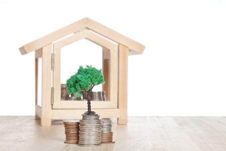 Real estate concept. House with coins stack