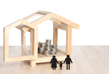 Real estate concept. Paper cut of family with house and coins stack