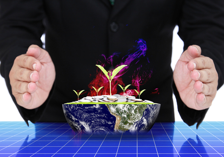Business man hands with plant growing out of coins on earth. (Elements of this image furnished by NASA)